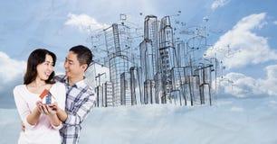 Imagen compuesta de Digitaces de los pares que llevan a cabo el modelo de la casa contra edificios en cielo fotografía de archivo