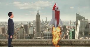 Imagen compuesta de Digitaces del hombre de negocios que mira el lanzamiento del cohete en ciudad Imagen de archivo libre de regalías