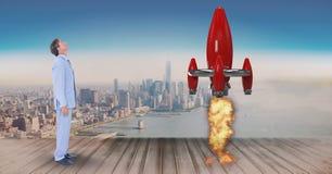 Imagen compuesta de Digitaces del hombre de negocios que mira el lanzamiento del cohete mientras que se opone en entarimado a Imagenes de archivo