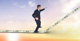 Imagen compuesta de Digitaces del hombre de negocios que se coloca en la calzada del dinero Imágenes de archivo libres de regalías