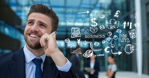 Imagen compuesta de Digitaces del hombre de negocios usando el teléfono elegante por los iconos Imagen de archivo