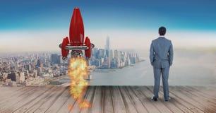 Imagen compuesta de Digitaces del lanzamiento del cohete del hombre de negocios que hace una pausa en el embarcadero mientras que Imagen de archivo libre de regalías