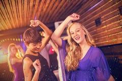 Imagen compuesta de dos mujeres hermosas que bailan en sala de baile Foto de archivo libre de regalías