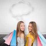 Imagen compuesta de dos mujeres jovenes con los panieres con la burbuja del discurso Foto de archivo libre de regalías