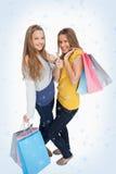 Imagen compuesta de dos mujeres jovenes hermosas con los panieres el thumbup Fotografía de archivo