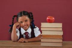 Imagen compuesta de la colegiala que se inclina por los libros y la manzana en el escritorio imagen de archivo
