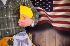 Imagen compuesta de la correa de la herramienta del trabajador que lleva manual mientras que sostiene el casco Fotos de archivo libres de regalías