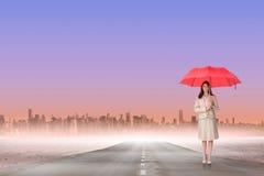 Imagen compuesta de la empresaria atractiva que sostiene el paraguas rojo Foto de archivo libre de regalías
