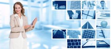 Imagen compuesta de la empresaria bonita feliz que sostiene una PC de la tableta foto de archivo