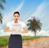 Imagen compuesta de la empresaria elegante chocada que sostiene el periódico Imagen de archivo