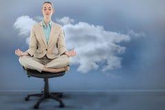 Imagen compuesta de la empresaria elegante pacífica que se sienta en la posición de loto respecto a silla de eslabón giratorio Fotografía de archivo