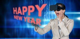 Imagen compuesta de la empresaria emocionada que señala mientras que lleva los vidrios video virtuales Imagen de archivo libre de regalías