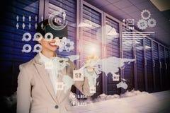 Imagen compuesta de la empresaria sonriente que señala mientras que lleva los vidrios video virtuales Fotos de archivo libres de regalías