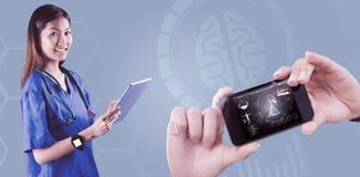 Imagen compuesta de la enfermera asiática que usa la tableta Imágenes de archivo libres de regalías