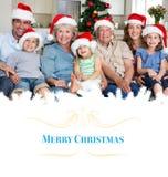 Imagen compuesta de la familia en los sombreros de santa que celebra la Navidad imagenes de archivo