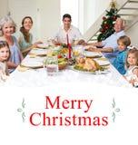 Imagen compuesta de la familia que tiene comida de la Navidad junto imagen de archivo libre de regalías
