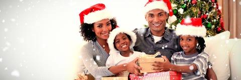 Imagen compuesta de la familia sonriente que comparte regalos de Navidad imagen de archivo libre de regalías
