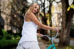 Imagen compuesta de la imagen compuesta digital de ir rubio en un paseo de la bici Foto de archivo libre de regalías