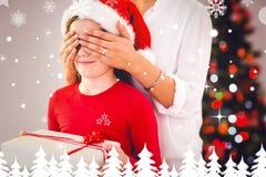 Imagen compuesta de la madre asombrosamente su hija con el regalo de la Navidad Foto de archivo