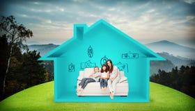 Imagen compuesta de la madre con sus niños que se sientan en el sofá Foto de archivo libre de regalías
