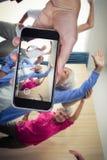 Imagen compuesta de la mano que sostiene el teléfono móvil contra el fondo blanco imagen de archivo