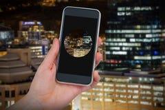 Imagen compuesta de la mano que sostiene el teléfono móvil contra el fondo blanco Foto de archivo libre de regalías