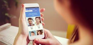 Imagen compuesta de la mano que sostiene smartphone Imágenes de archivo libres de regalías