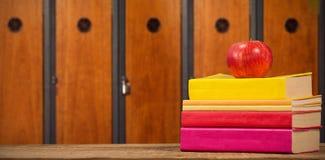 Imagen compuesta de la manzana con los libros en la tabla de madera Imagen de archivo libre de regalías