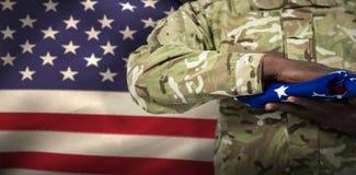 Imagen compuesta de la mediados de sección del soldado que sostiene la bandera americana imagen de archivo