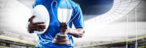 Imagen compuesta de la mediados de sección del deportista que sostiene el trofeo y la bola de rugbi imagenes de archivo