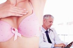 Imagen compuesta de la mediados de sección de la mujer en el sujetador para la conciencia del cáncer de pecho Foto de archivo