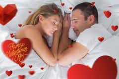 Imagen compuesta de la mentira linda de los pares dormida en cama Fotos de archivo