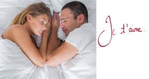 Imagen compuesta de la mentira linda de los pares dormida en cama Fotografía de archivo libre de regalías