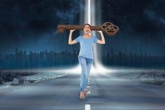 Imagen compuesta de la morenita enfadada que lleva llave grande Foto de archivo libre de regalías