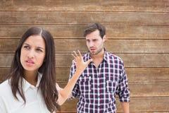 Imagen compuesta de la morenita enojada que no escucha su novio Foto de archivo