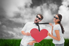 Imagen compuesta de la morenita que tira de su novio por el lazo que lleva a cabo el corazón Imágenes de archivo libres de regalías