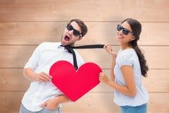 Imagen compuesta de la morenita que tira de su novio por el lazo que lleva a cabo el corazón Fotografía de archivo libre de regalías