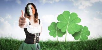 Imagen compuesta de la muchacha irlandesa que muestra los pulgares para arriba Fotografía de archivo