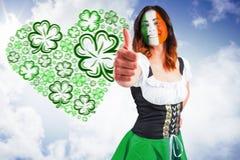 Imagen compuesta de la muchacha irlandesa que muestra los pulgares para arriba Foto de archivo
