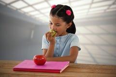 Imagen compuesta de la muchacha que come la manzana del granny smith en la tabla foto de archivo libre de regalías