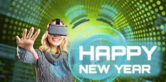 Imagen compuesta de la mujer alegre que usa las auriculares virtuales de la realidad Fotografía de archivo