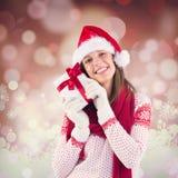 Imagen compuesta de la mujer atractiva que lleva el sombrero de santa con el regalo Imágenes de archivo libres de regalías