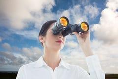Imagen compuesta de la mujer de negocios que mira a través de los prismáticos Fotos de archivo