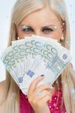 Imagen compuesta de la mujer de ojos verdes que sostiene 100 billetes de banco de los euros Imagen de archivo libre de regalías