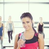 Imagen compuesta de la mujer del ajuste que sostiene la botella de agua Fotos de archivo libres de regalías