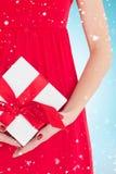 Imagen compuesta de la mujer en el vestido rojo que sostiene el regalo Imagen de archivo libre de regalías
