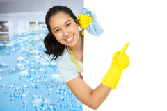 Imagen compuesta de la mujer en los guantes de goma que señala a la superficie blanca Foto de archivo