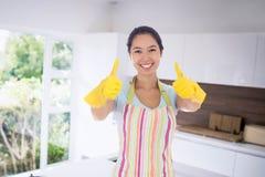 Imagen compuesta de la mujer feliz que da los pulgares para arriba en los guantes de goma Foto de archivo