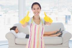 Imagen compuesta de la mujer feliz que da los pulgares para arriba en los guantes de goma Imágenes de archivo libres de regalías