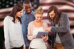 Imagen compuesta de la mujer feliz que sostiene la tableta digital y que la discute con los compañeros de trabajo fotografía de archivo libre de regalías